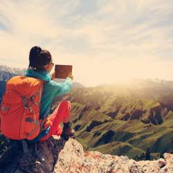 woman backpacker use digital tablet taking photo on mountain peak