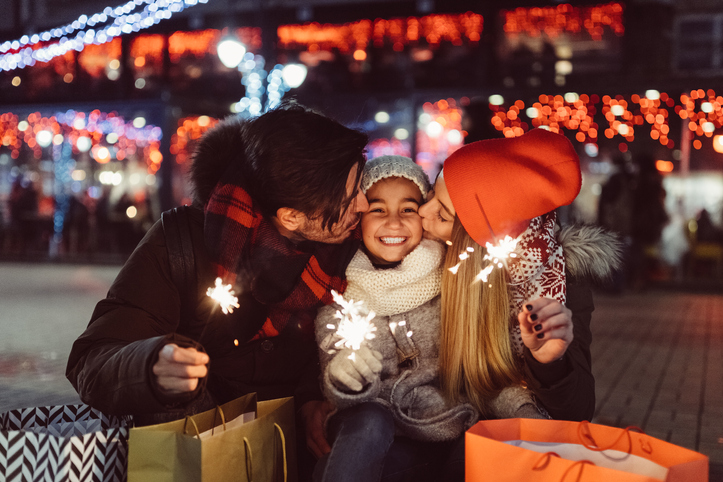 New Year's family pictures include Mom and Dad kissing daughter at midnight with sparklers.