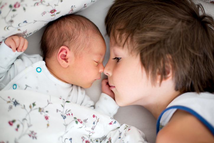 Capture those first special moments between siblings.