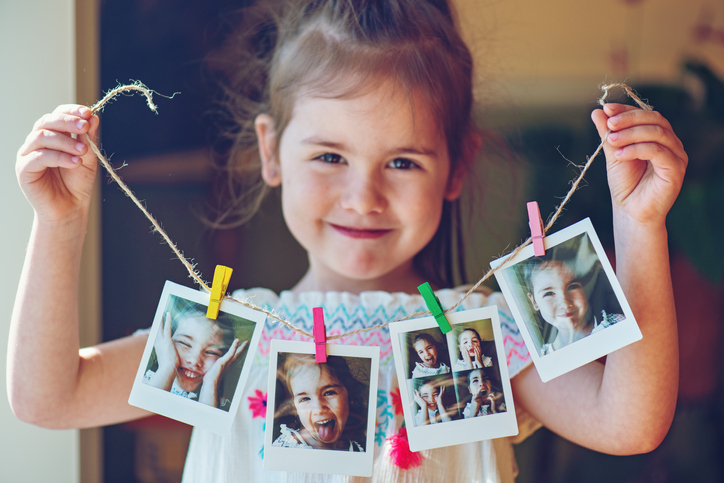 Little girl holds up photography gifts she made of Polaroids on a string.