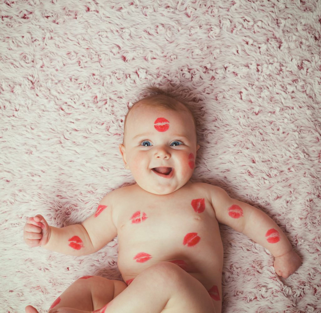 Newborn baby girl on the soft blanket filled kisses made with the lipstick.