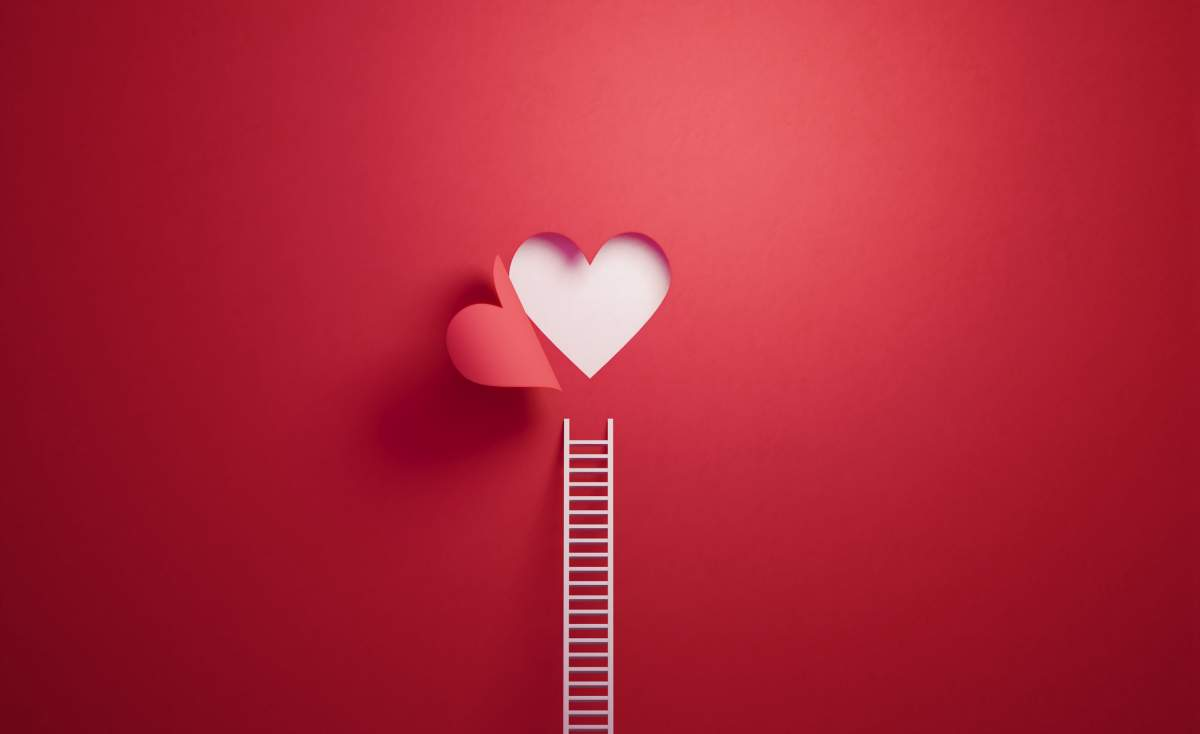 White Ladder Leaning on Red Wall with Cut Out Heart Shape