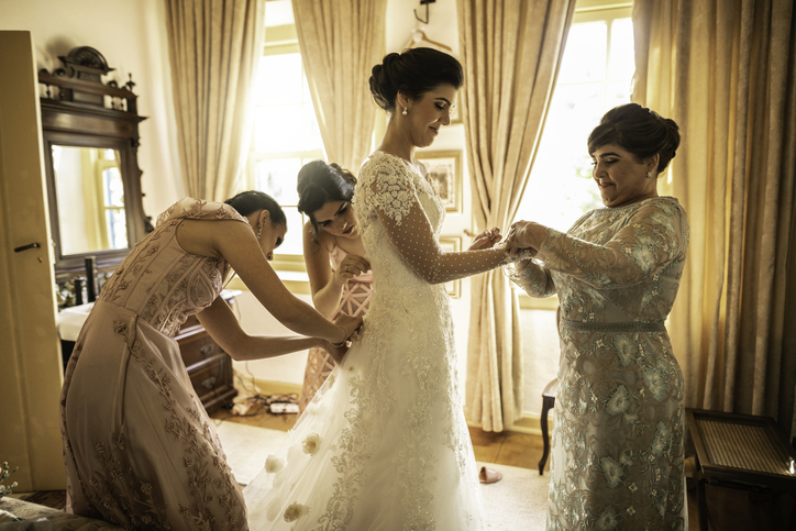 Classic wedding photos include helping the bride get dressed for her big day.