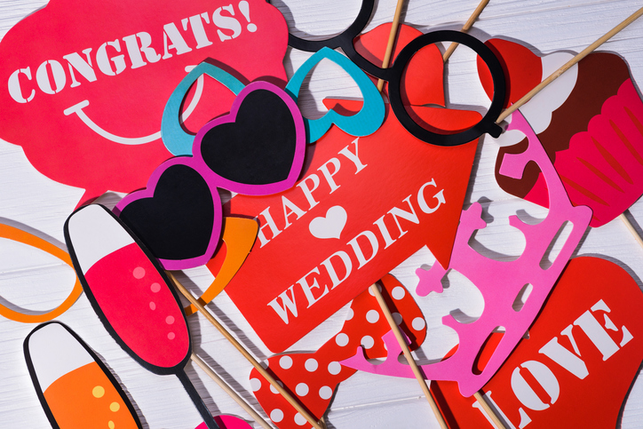 A wedding photo booth uses fun props to liven up photos.