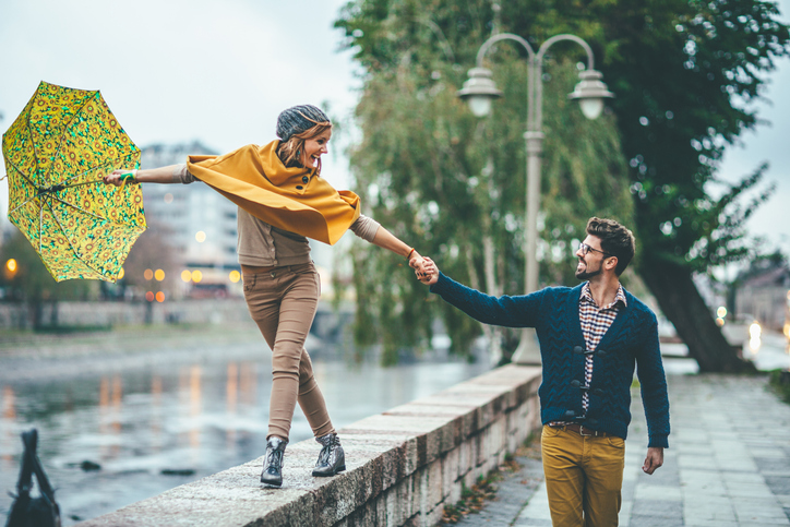 An engagement photo shoot in the rain can bring out the playful side of a couple.