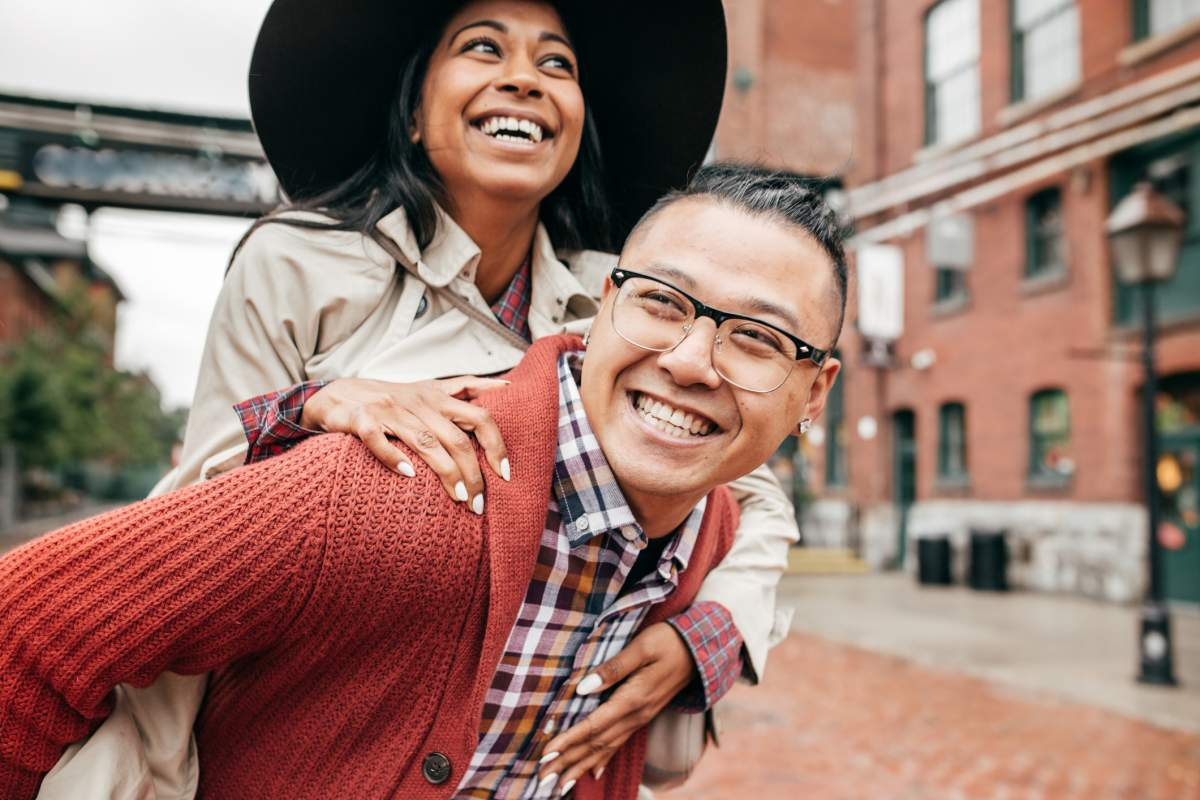 Romantic engagement photos include playful walks outside.