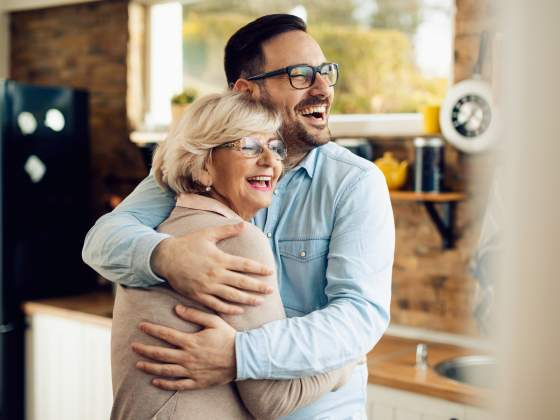 Cheerful man and his mature mother embracing in the kitchen.