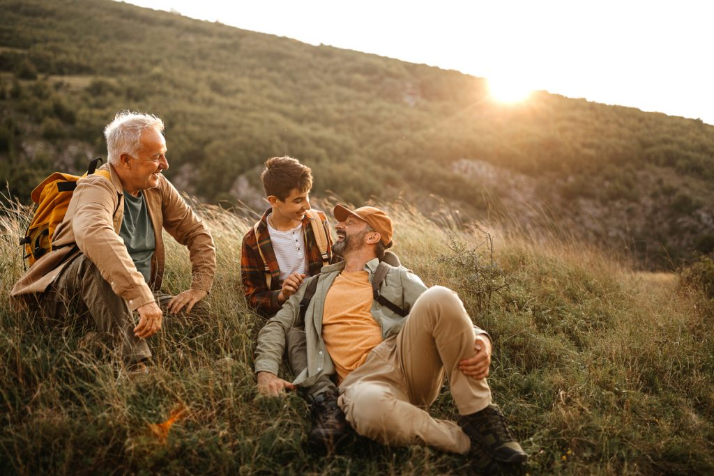 Elderly father with adult son and grandson relaxing in nature during hiking tour