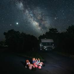 Family lies on the ground by RV looking at the stars