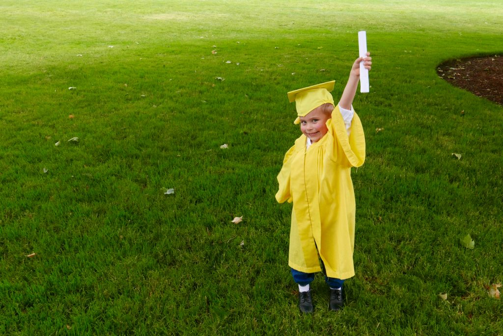 Boy graduating from preschool holds up his diploma