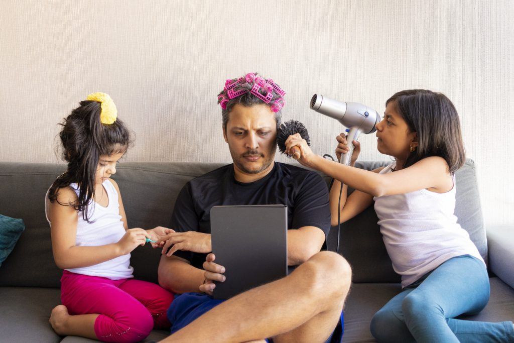 Pretty daughters are painting the nails and combing the hair of their handsome young father