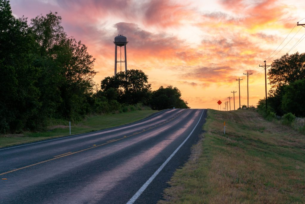 Up Hill Road Towards the Horizon With Water Tower Above the Trees in a Colorful Sunset