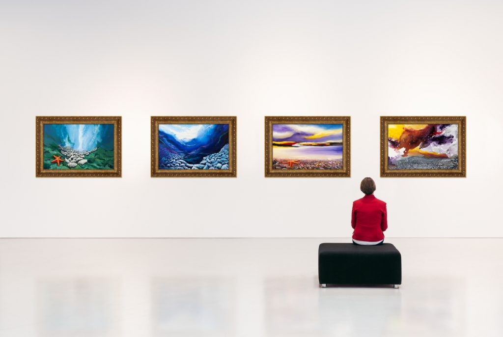 Exhibition centre, a visitor visits an art exhibition and looks at artist's collection on the wall. Documentation on file for artwork.