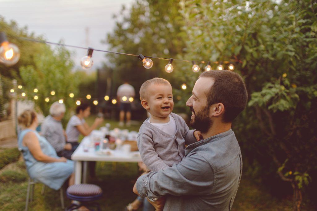 Photo of a multi-generation family having dinner outdoors in their back yard, while their little boy is celebrating his birthday
