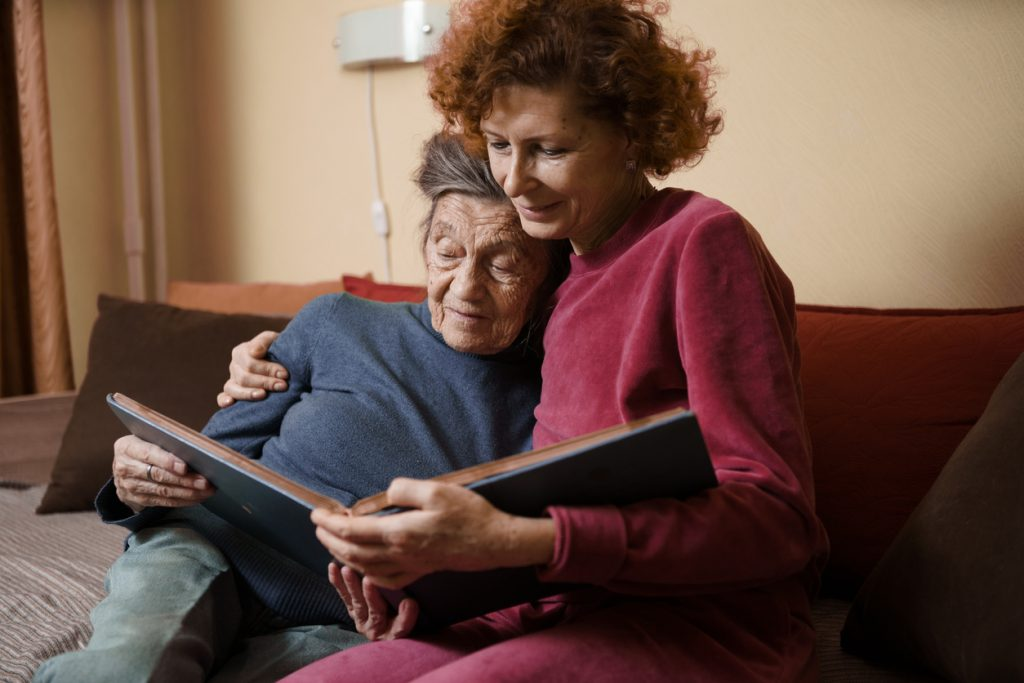 Senior woman and her adult daughter looking at photo album together on couch in living room, talking joyful discussing memories. Weekend with parents, family day, thanksgiving, mom's holiday.