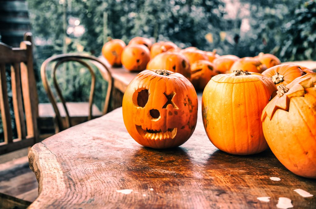 Table full of pumpkins already carved and ready for Halloween.