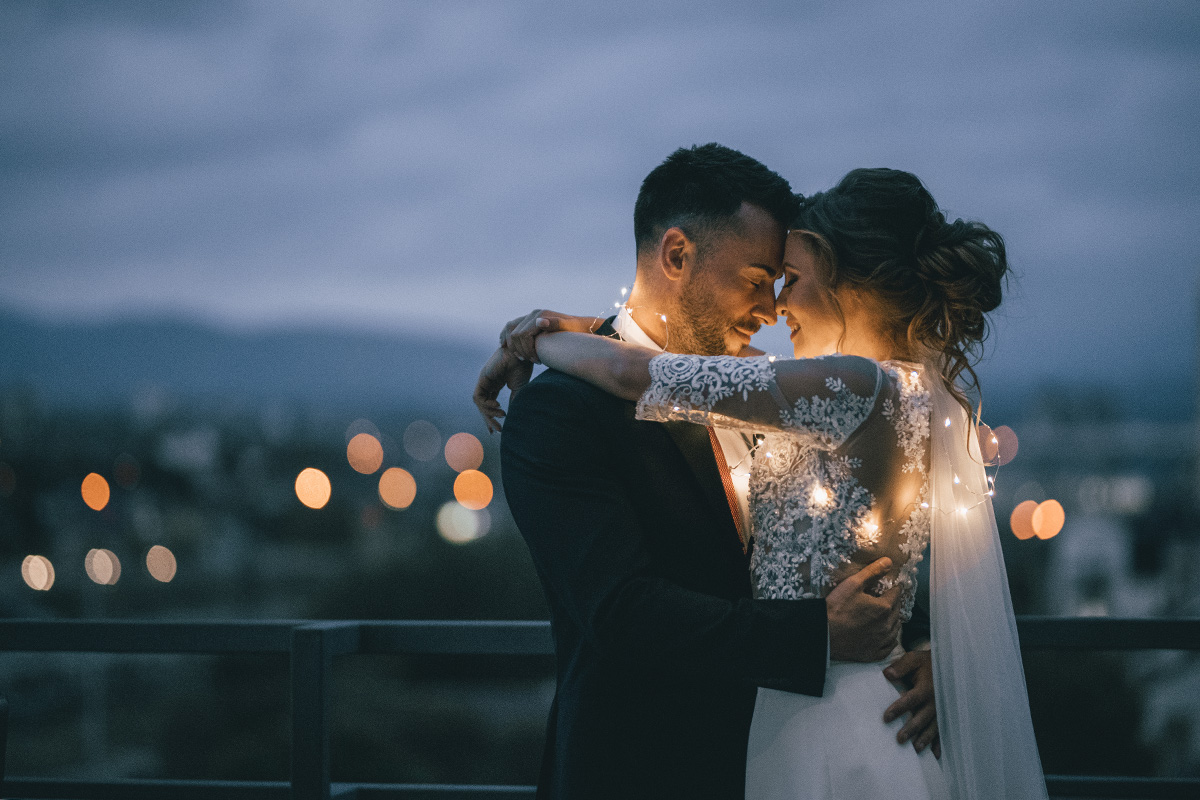 A bride and groom hugging outside with lights on the brides dress | Motif