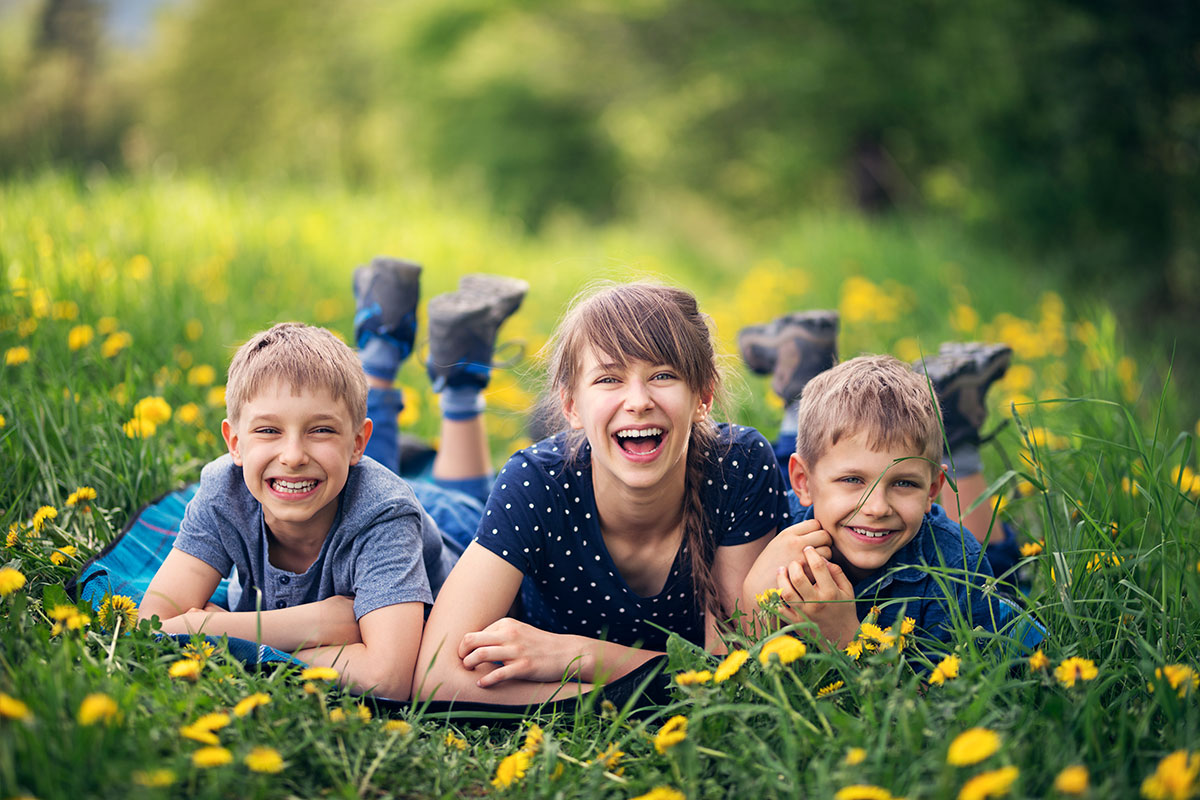 A family portrait of three kids laying down on a blanket surrounded by sunflowers | Motif