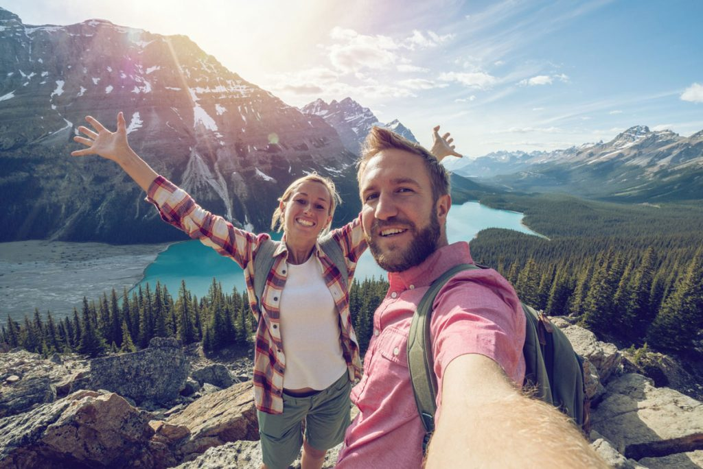 A couple taking a selfie on top of a mountain   Motif