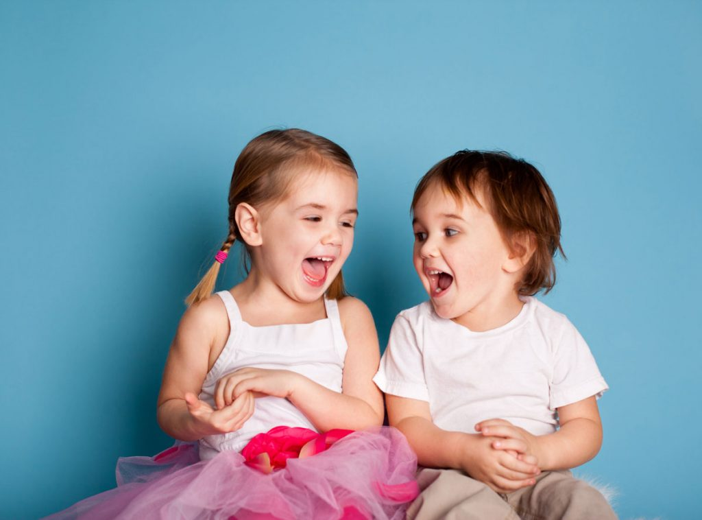 Two kids laughing while getting their picture taken | Motif