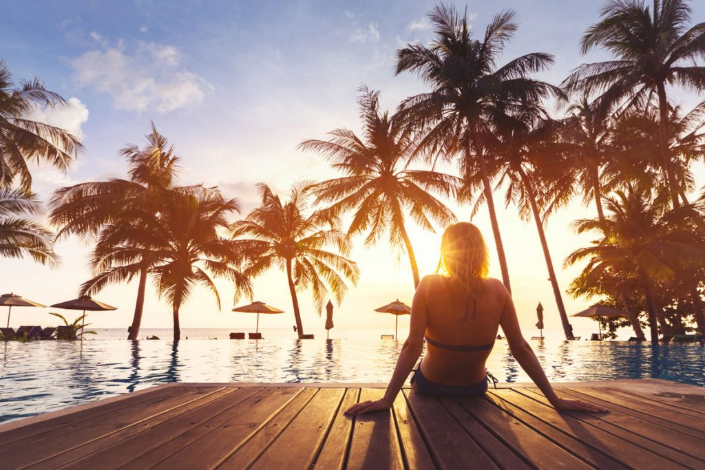 A girl sitting on the edge of a pool while the sun is setting | Motif